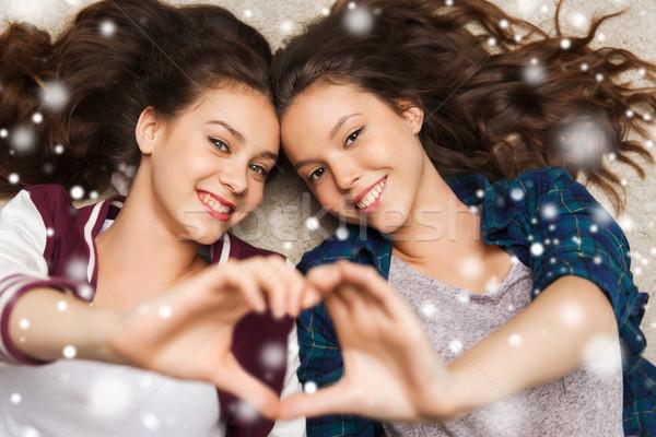 happy teenage girls lying on floor with heart Stock photo © dolgachov