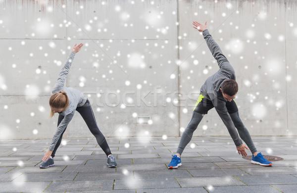 couple of sportsmen stretching on city street Stock photo © dolgachov