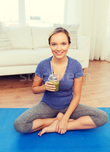 happy woman with smoothie sitting on mat at home Stock photo © dolgachov