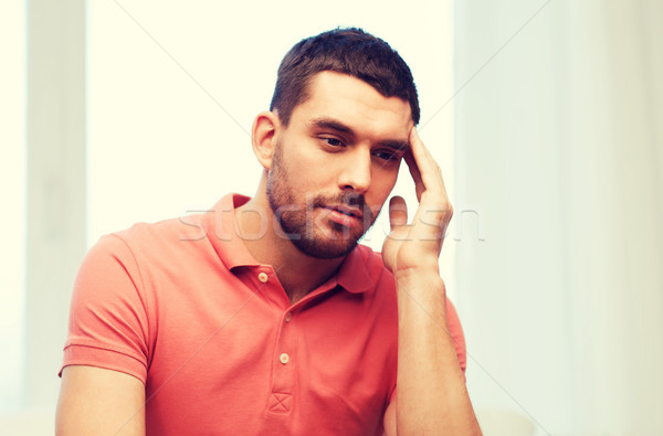 unhappy man suffering from headache at home Stock photo © dolgachov