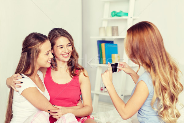 teen girls with smartphone taking picture at home Stock photo © dolgachov