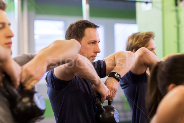 group of people with kettlebells exercising in gym Stock photo © dolgachov