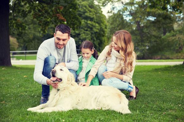 Stock photo: happy family with labrador retriever dog in park
