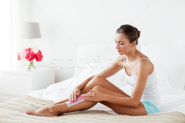 woman epilating leg hair with wax strip at home Stock photo © dolgachov