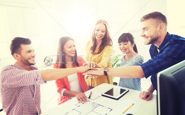 creative team holding hands together  at office Stock photo © dolgachov