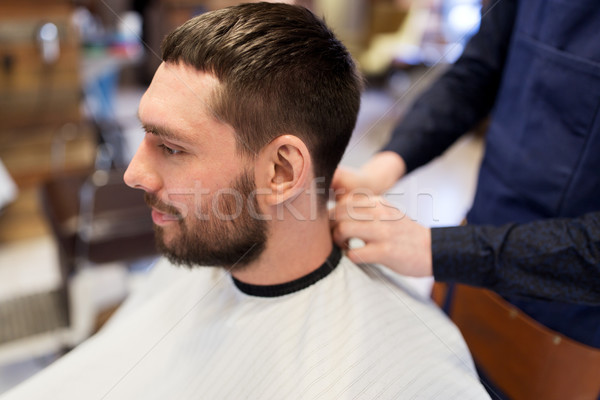 hairdresser and man with beard at barbershop Stock photo © dolgachov