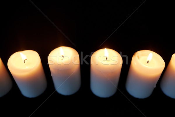 candles burning in darkness over black background Stock photo © dolgachov