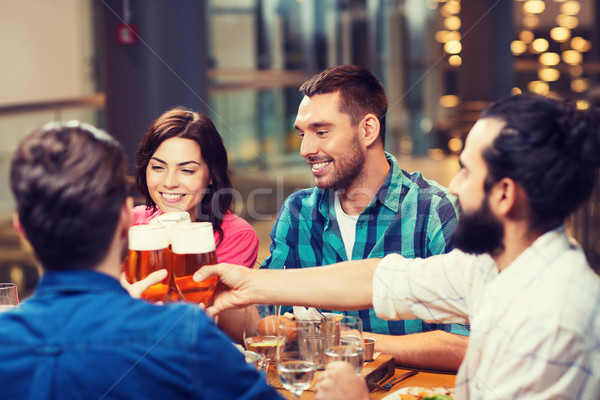 friends dining and drinking beer at restaurant Stock photo © dolgachov