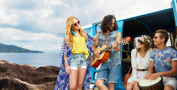 hippie friends playing music at minivan on island Stock photo © dolgachov