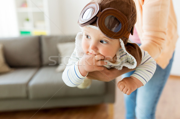 happy mother with baby wearing pilot hat at home Stock photo © dolgachov
