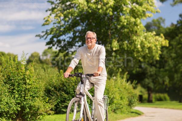 happy senior man riding bicycle at summer park Stock photo © dolgachov