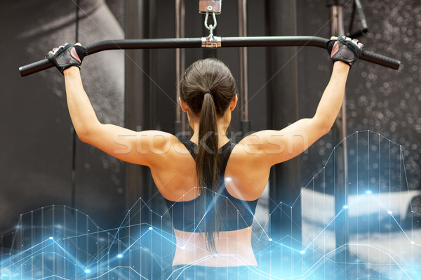 woman flexing muscles on cable machine in gym Stock photo © dolgachov