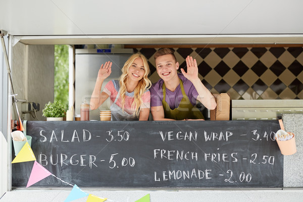 happy couple of sellers waving hands at food truck Stock photo © dolgachov