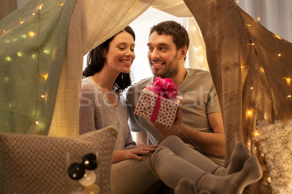 happy couple with gift box in kids tent at home Stock photo © dolgachov