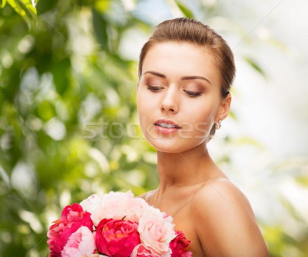 Frau tragen Ohrringe halten Blumen Schönheit Stock foto © dolgachov