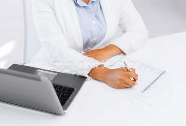 businesswoman writing something Stock photo © dolgachov