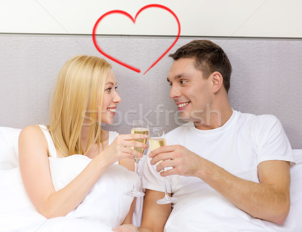 smiling couple with champagne glasses in bed Stock photo © dolgachov