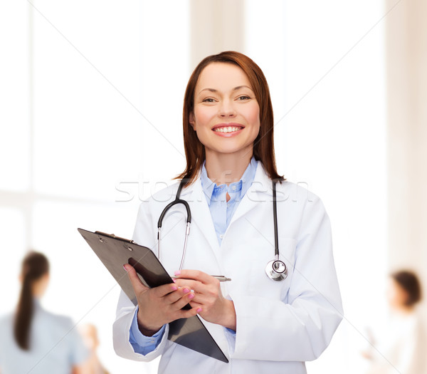 smiling female doctor with clipboard Stock photo © dolgachov