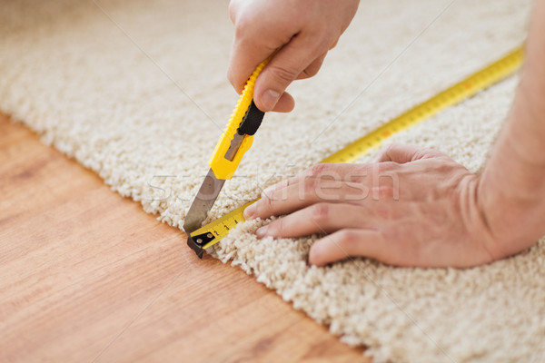 close up of male hands cutting carpet Stock photo © dolgachov