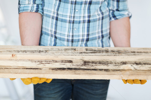 close up of male in gloves carrying wooden boards Stock photo © dolgachov