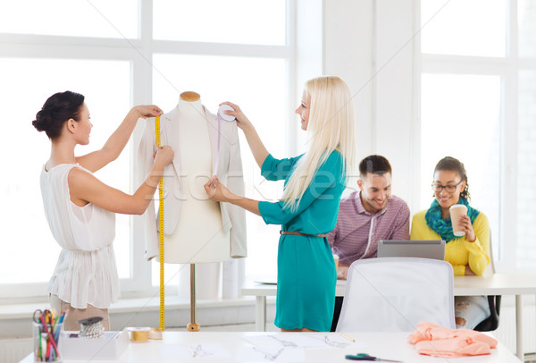 fashion designers measuring jacket on mannequin Stock photo © dolgachov