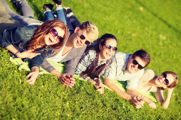 group of students or teenagers lying in park Stock photo © dolgachov
