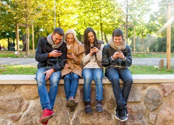 Mosolyog barátok okostelefonok város park utazás Stock fotó © dolgachov