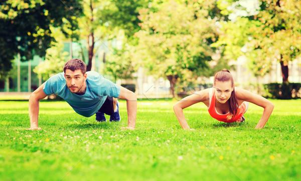 couple doing push-ups outdoors Stock photo © dolgachov