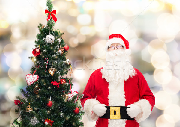 man in costume of santa claus with christmas tree Stock photo © dolgachov