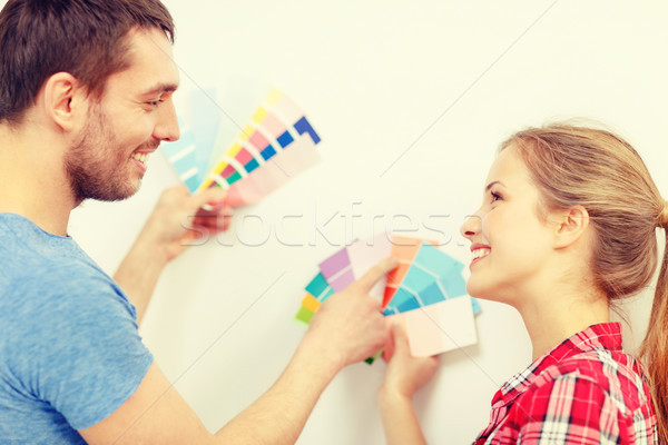 Stock photo: smiling couple looking at color samples at home