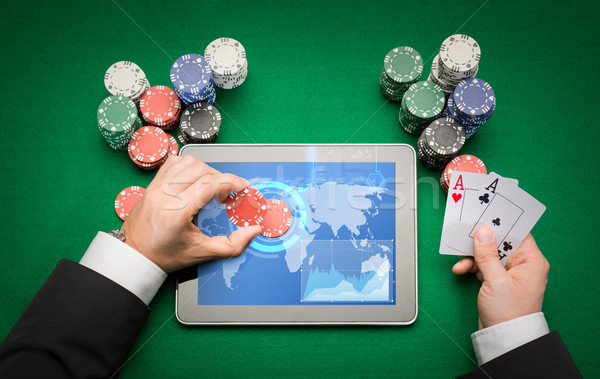 casino poker player with cards, tablet and chips Stock photo © dolgachov