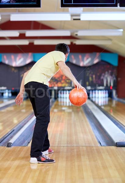 happy young man throwing ball in bowling club Stock photo © dolgachov