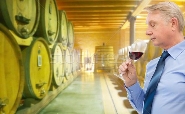 senior man smelling red wine in cellar Stock photo © dolgachov