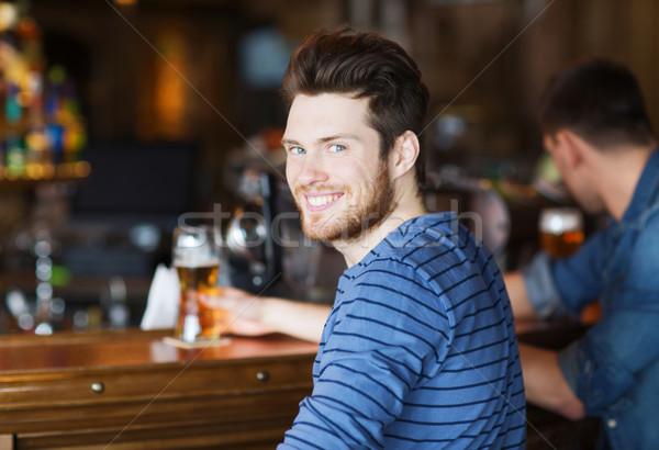 Glücklich junger Mann trinken Bier bar Veröffentlichung Stock foto © dolgachov