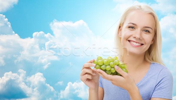 happy woman eating grapes over sky Stock photo © dolgachov