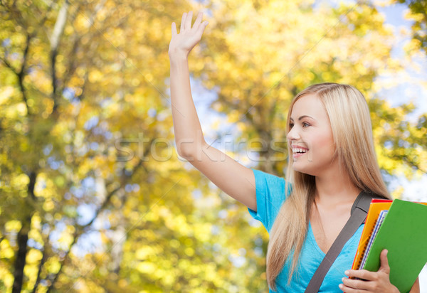 student with folders waving hand over autumn park Stock photo © dolgachov