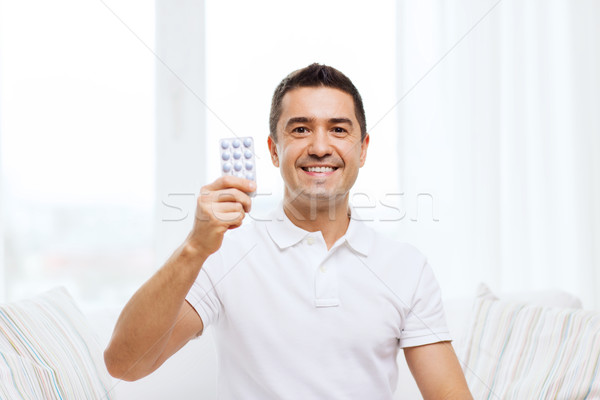 happy man showing pack of pills at home Stock photo © dolgachov