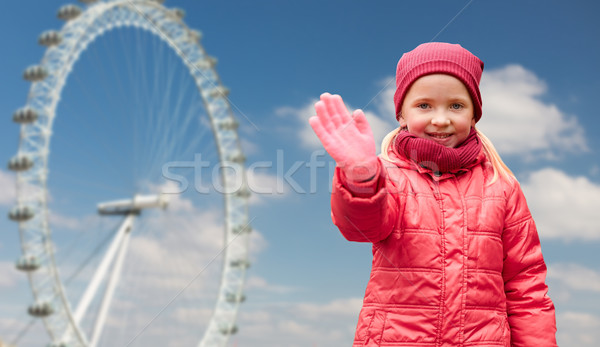 happy little girl waving hand over ferry wheel Stock photo © dolgachov