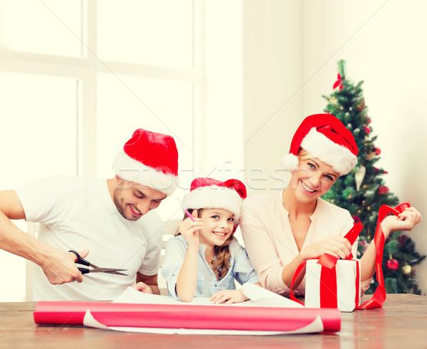 happy family in santa helper hats packing gift Stock photo © dolgachov