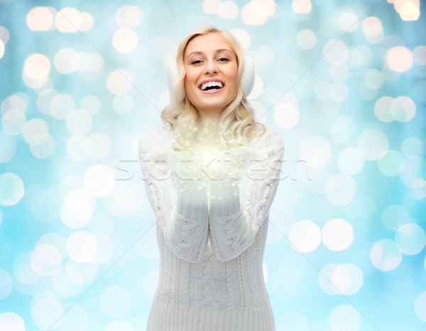 woman in winter earmuffs holding fairy dust Stock photo © dolgachov