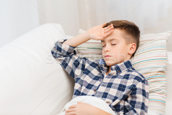 ill boy lying in bed and suffering from headache Stock photo © dolgachov