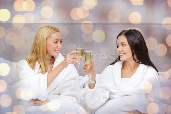 Stock photo: smiling girlfriends with champagne glasses in bed