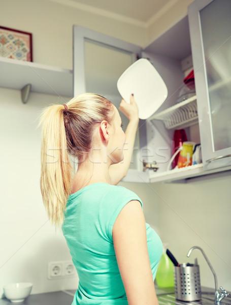 happy woman putting plate to kitchen cabinet Stock photo © dolgachov