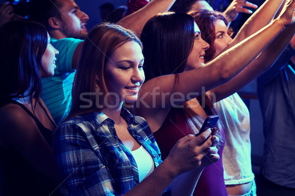 woman with smartphone texting message at concert Stock photo © dolgachov