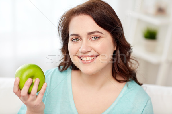 happy plus size woman eating green apple at home Stock photo © dolgachov