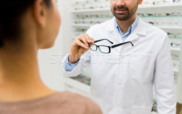 close up of optician with glasses at optics store Stock photo © dolgachov