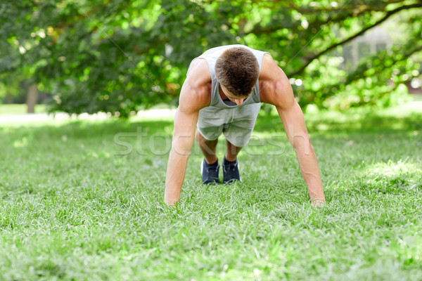 young man doing push ups on grass in summer park Stock photo © dolgachov
