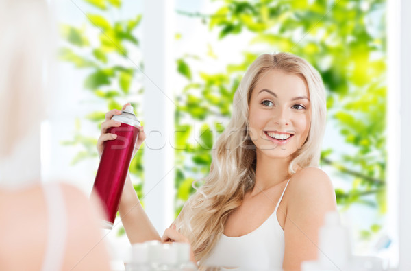 woman with hairspray styling her hair at bathroom Stock photo © dolgachov