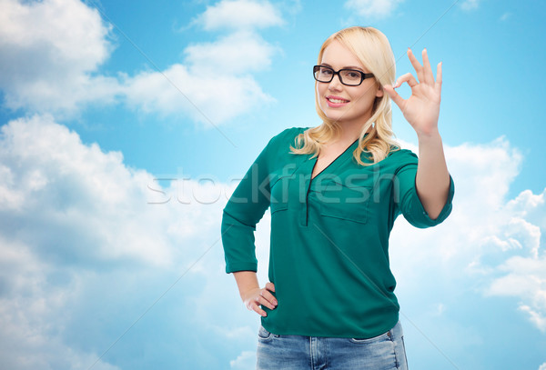 smiling young woman with eyeglasses showing ok Stock photo © dolgachov
