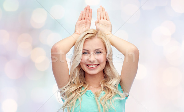 happy smiling young woman making bunny ears Stock photo © dolgachov